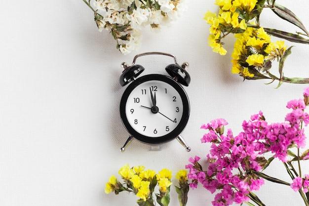 Mudança de horário de primavera com despertador e galhos de flores Foto Premium