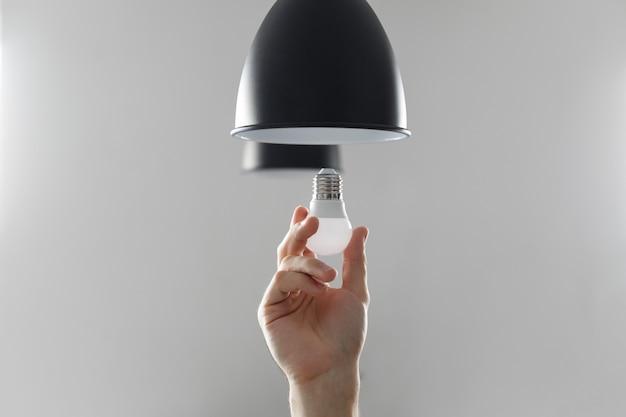 Mudando o bulbo para o bulbo conduzido na lâmpada de assoalho na cor preta. Foto Premium