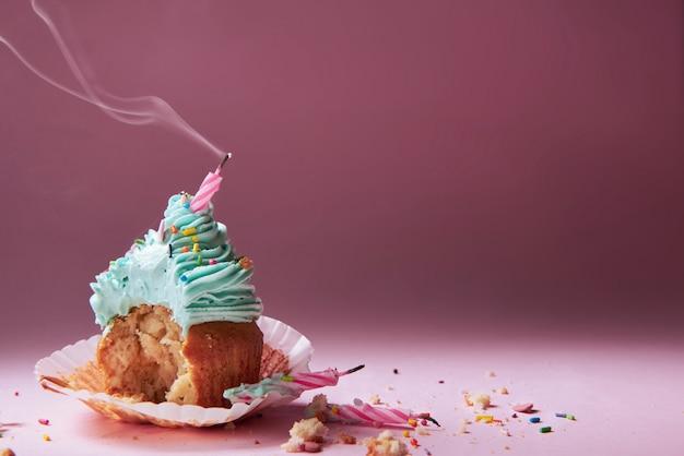 Muffin com creme e vela apagada. o conceito do fim da celebração. Foto Premium