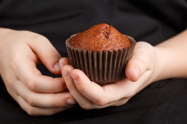 Muffin de chocolate caseiro nas mãos das crianças Foto Premium