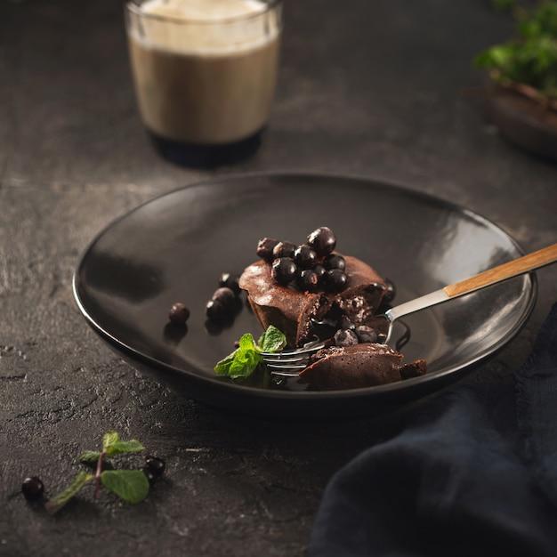 Muffin de chocolate com mirtilos em chapa preta sobre fundo escuro com café Foto Premium