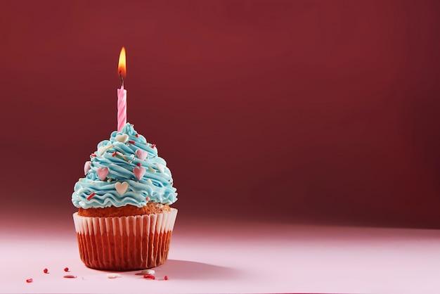 Muffin ou um pequeno bolo com uma vela acesa. conceito de parabéns, feriado. Foto Premium