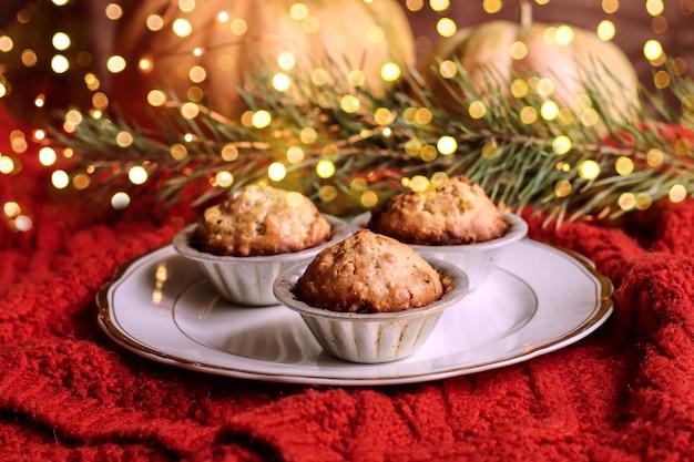 Muffins, bolos com nozes na sala de fundo decorada para o natal. Foto Premium
