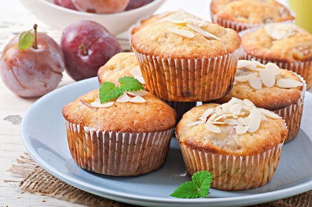 Muffins com ameixas e pétalas de amêndoa, decoradas com folhas de hortelã Foto gratuita