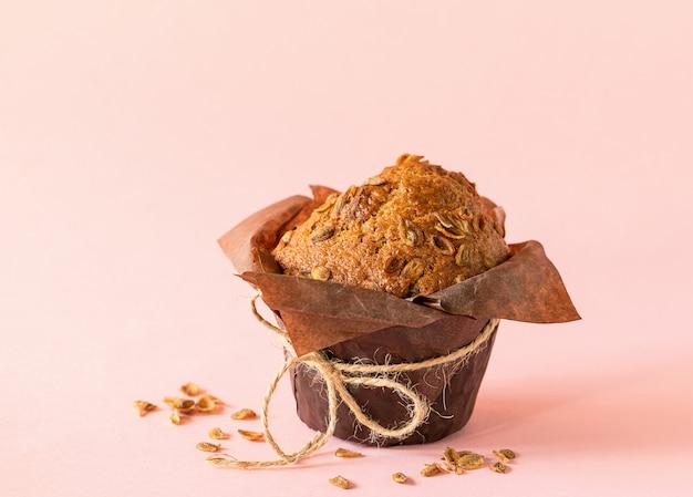 Muffins com flocos de trigo em close-up de embalagem de papel marrom no fundo rosa. sobremesa saudável vegan. Foto Premium