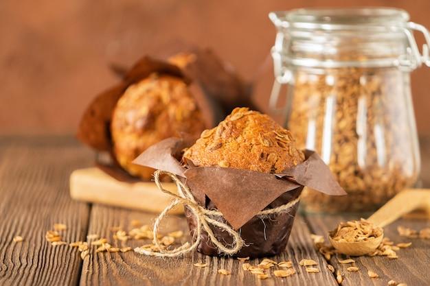 Muffins com flocos de trigo em papel marrom fundo de madeira close-up de embalagem. sobremesa saudável vegan. Foto Premium
