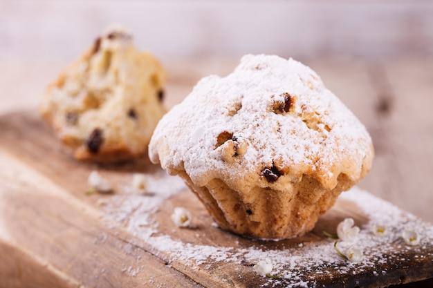 Muffins com passas polvilhadas com açúcar em pó. Foto Premium