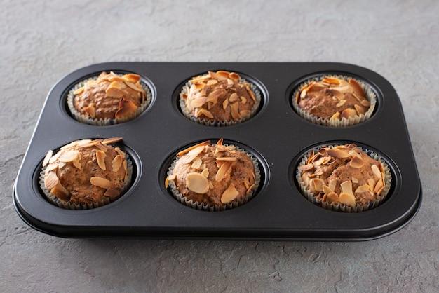 Muffins com queijo cottage decorado com flocos de amêndoa em uma assadeira. Foto Premium