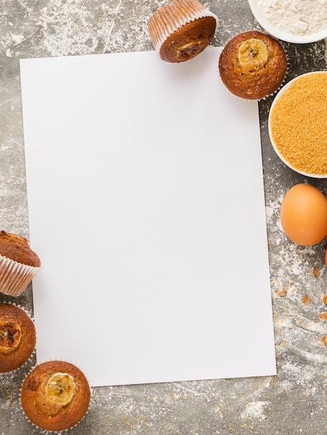 Muffins de banana caseiros e ingredientes para cozinhar são dispostos em uma folha em branco branca. sobremesa saudável vegan. Foto Premium