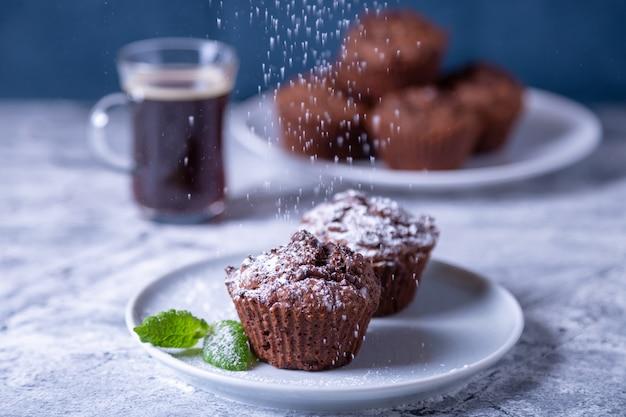 Muffins de chocolate com hortelã em um prato preto, espalhado com açúcar de confeiteiro. cozimento caseiro. no fundo, há uma xícara de café e um prato com muffins. mesa de mármore e fundo azul. Foto Premium