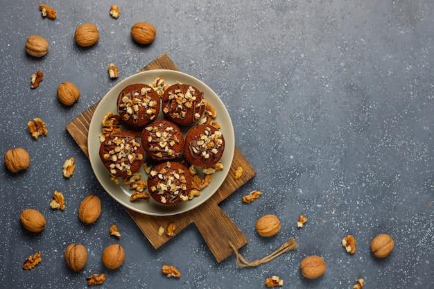 Muffins de chocolate e nozes com uma xícara de café com nozes na superfície escura Foto gratuita