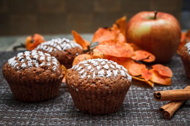 Muffins de chocolate em um fundo de folhas de outono e canela Foto Premium