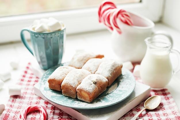Muffins de natal, leite, cacau, marshmallows, pirulitos de doces em um prato branco perto da janela Foto Premium