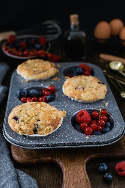 Muffins de streusel com mirtilo, framboesa e groselha na mesa de madeira rústica Foto Premium