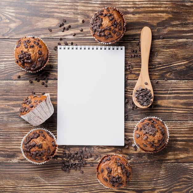 Muffins de vista superior deliciosa com bloco de notas Foto gratuita
