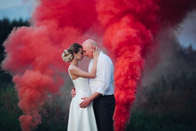 Muita fumaça vermelha e branca perto de uma linda mulher de vestido branco e um homem caucasiano de camisa branca e calça preta Foto Premium