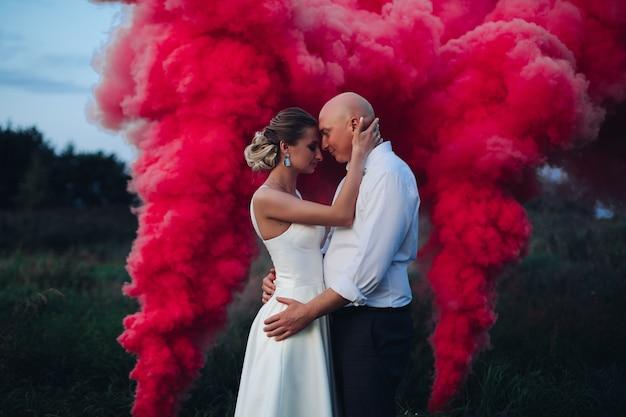 Muita fumaça vermelha perto de uma mulher bonita em um vestido branco e um homem caucasiano de camisa branca e calça preta Foto Premium