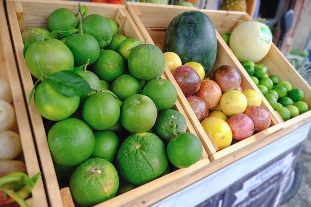 Muita tangerina e muitas frutas misturadas em uma cesta de cabelo de madeira. Foto Premium