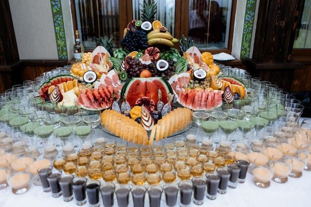 Muita variedade de frutas e bebidas servidas em uma mesa de comemoração Foto gratuita