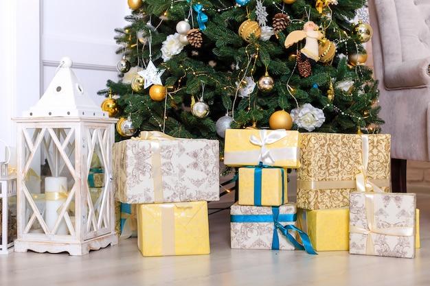Muitas caixas com presentes christas perto da árvore Foto Premium