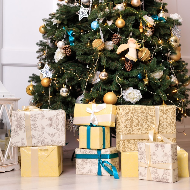 Muitas caixas com presentes dos christas perto da árvore. moldura quadrada. Foto Premium