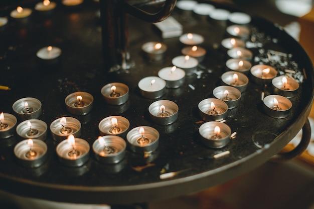 Muitas chamas de velas brilhando no escuro criam uma atmosfera espiritual. Foto Premium