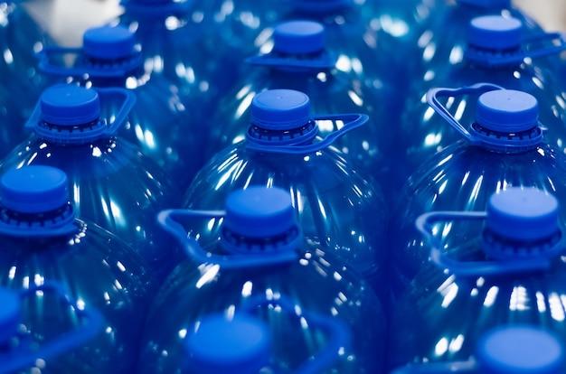 Muitas garrafas de plástico líquido químico azul. grupo de garrafas em close Foto Premium