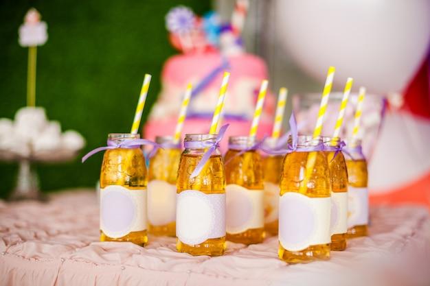 Muitas garrafas de suco de maçã, rótulos especiais, palhas brancas e amarelas, bolo rosa grande e balões brancos e roxos Foto Premium