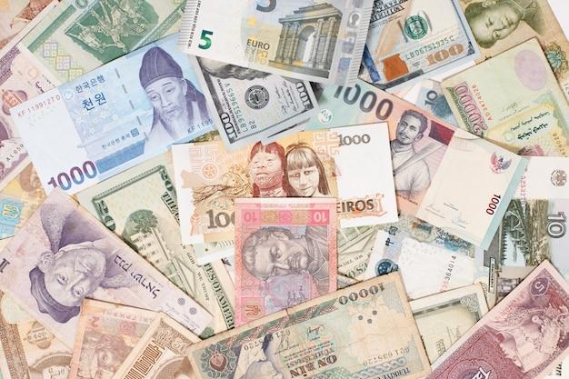 Muitas moedas diferentes como dinheiro global do conceito de plano de fundo colorido Foto Premium