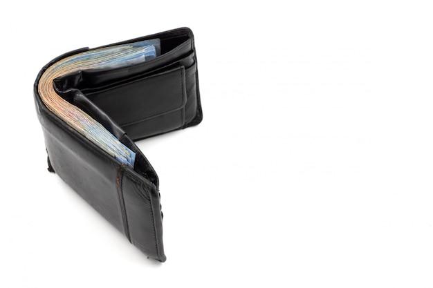 Muitas notas de banco na carteira preta no fundo branco. copie o espaço Foto Premium