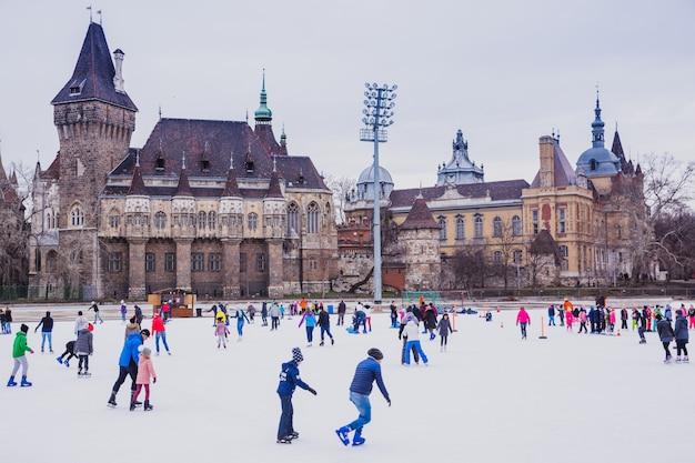 Muitas pessoas passam suas férias patinando na pista de gelo do parque da cidade em budapeste, em frente ao castelo de vajdahunyad, hungria Foto Premium