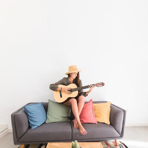 Muito adolescente usando chapéu tocando violão em casa Foto gratuita