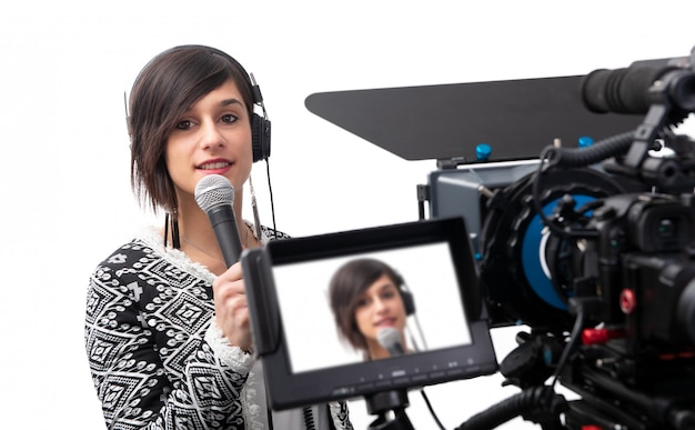 Muito jovem jornalista apresentando relatório no estúdio de televisão em branco Foto Premium