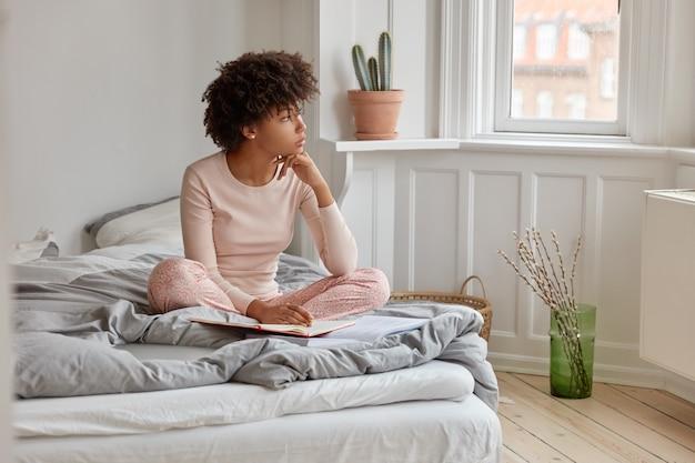 Muito jovem, morena, com corte de cabelo afro, escreve em diário, tem expressão sonhadora, usa pijama, posa na cama em um quarto espaçoso, pensando profundamente antes de dormir. conceito de cama Foto gratuita