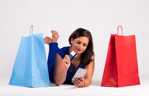 Muito jovem mulher caucasiana, deitado no chão, olhando para o telefone móvel e usando o cartão de crédito Foto Premium
