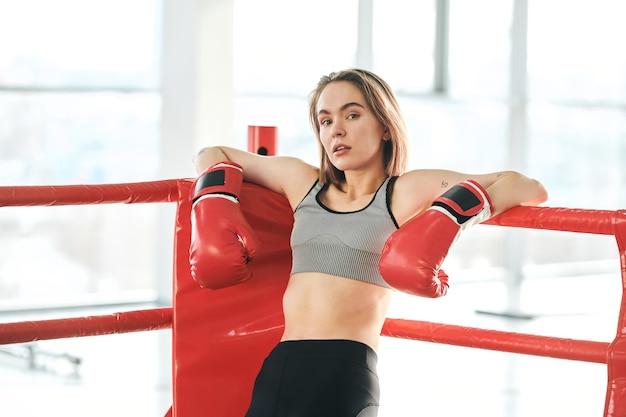 Muito jovem mulher com luvas de boxe vermelhas e agasalho, olhando para você enquanto se inclina contra as barras do ringue no ginásio Foto Premium