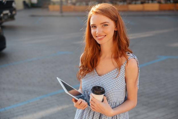 Muito jovem, segurando o tablet pc e café Foto gratuita