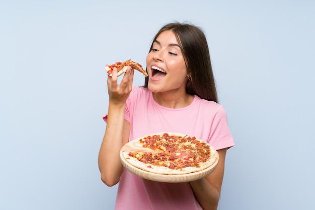 Muito jovem, segurando uma pizza sobre parede azul isolada Foto Premium