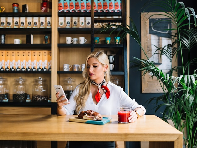 Muito jovem, usando telefone celular, segurando o copo de suco no café Foto gratuita