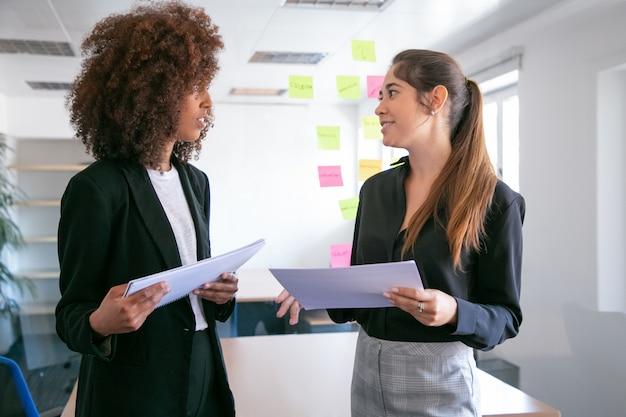 Muito jovens empresárias discutindo o plano do projeto e sorrindo. duas belas colegas femininas segurando documentos e conversando na sala de conferências. conceito de trabalho em equipe, negócios e gestão Foto gratuita