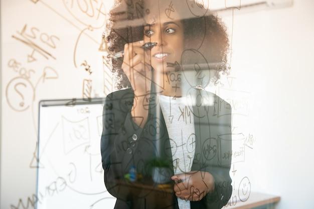 Muito jovens empresárias escrevendo na placa de vidro. confiante experiente gerente feminina afro-americana segurando o marcador e sorrindo na sala do escritório. estratégia, negócios e conceito de gestão Foto gratuita