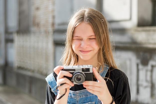 Muito linda garota jovem segurando a câmera retro Foto gratuita