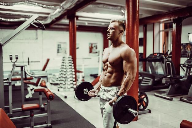 Muito poder cara fisiculturista, executar exercícios com halteres Foto Premium