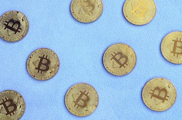 Muitos bitcoins dourados encontram-se em um cobertor feito de tecido de lã azul claro macio e fofo Foto Premium