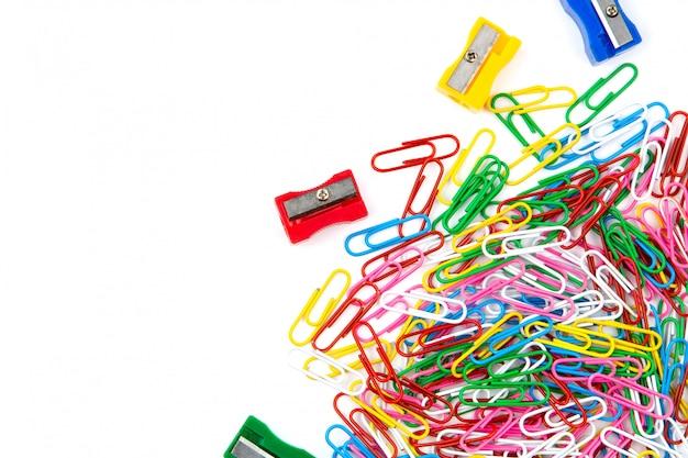 Muitos clipes de papel e sharpeners coloridos em um fundo branco. vista superior e espaço de cópia. Foto Premium