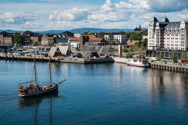 Muitos edifícios na costa de um mar perto da fortaleza de akershus em oslo, noruega Foto gratuita