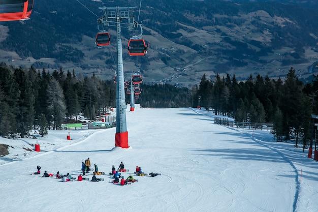 Muitos esquiadores e praticantes de snowboard descansam em uma ladeira na estação de esqui Foto Premium