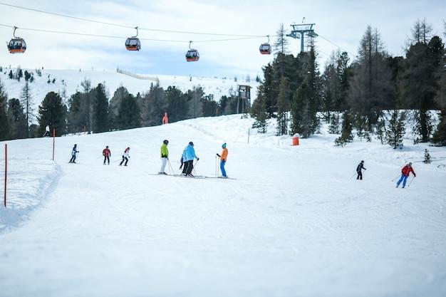 Muitos esquiadores montam nos alpes em dia ensolarado de inverno. teleférico nas montanhas. Foto Premium