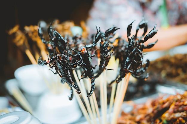 Muitos fritaram o escorpião em espetos na estrada de yaowarat no bairro chinês em banguecoque, tailândia. Foto Premium