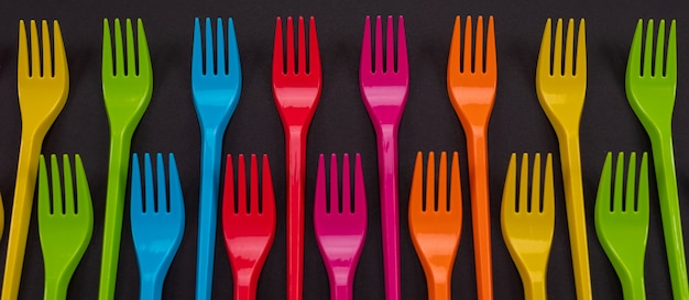 Muitos garfos de plástico de cor sobre um fundo brilhante Foto Premium